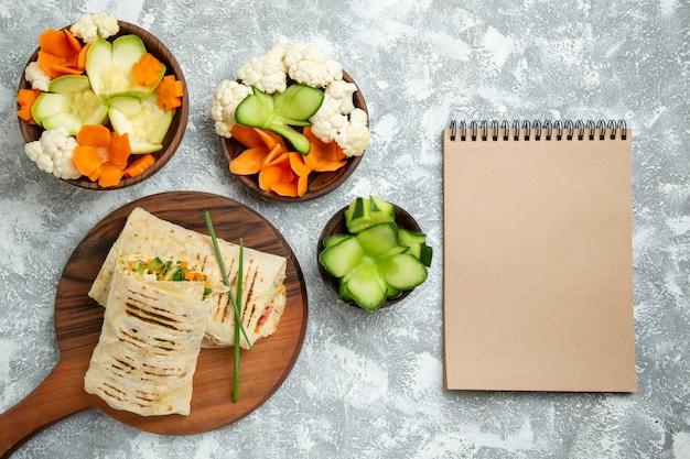 Bovenaanzicht gesneden sandwich met groenten op witte achtergrond brood maaltijd sandwich hamburger eten