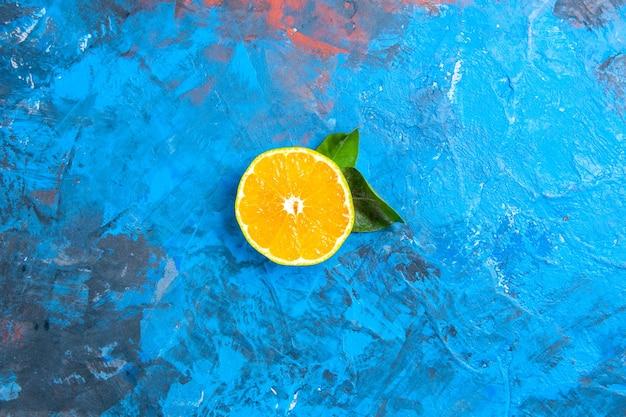 Bovenaanzicht gesneden sinaasappel op blauw oppervlak met vrije ruimte