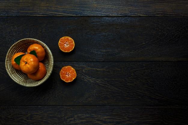 Bovenaanzicht gesneden sinaasappel op rustieke houten en mand met kopie ruimte.