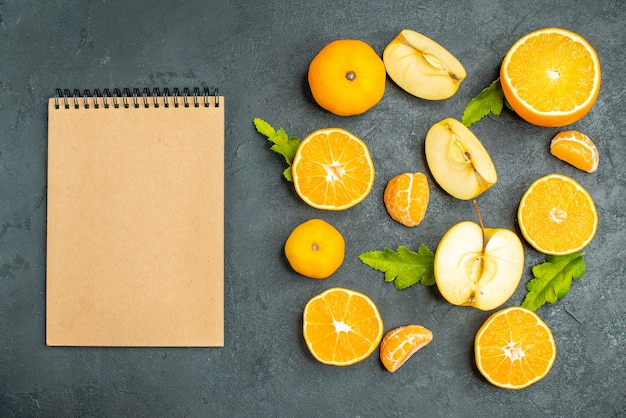 Bovenaanzicht gesneden sinaasappelen en appels een notitieboekje op donkere achtergrond