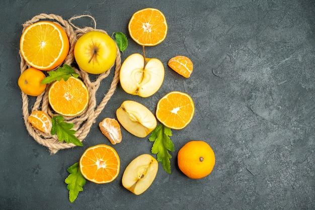 Bovenaanzicht gesneden sinaasappelen en appels op donkere achtergrond