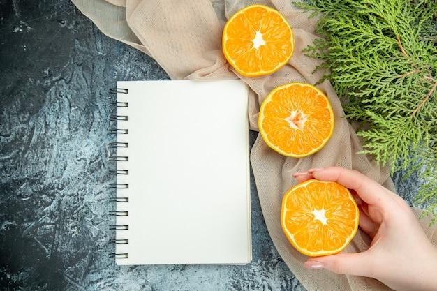 Bovenaanzicht gesneden sinaasappelen in vrouwelijke hand dennenappels op beige sjaal kladblok op donkere ondergrond