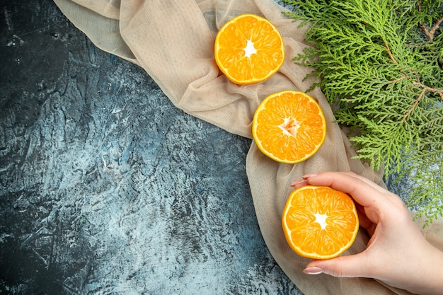 Bovenaanzicht gesneden sinaasappelen in vrouwelijke hand dennenappels op beige sjaal op donkere oppervlakte vrije ruimte