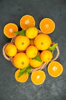 Bovenaanzicht gesneden sinaasappelen, mandarijnen en sinaasappelen in rieten mand op donkere achtergrond