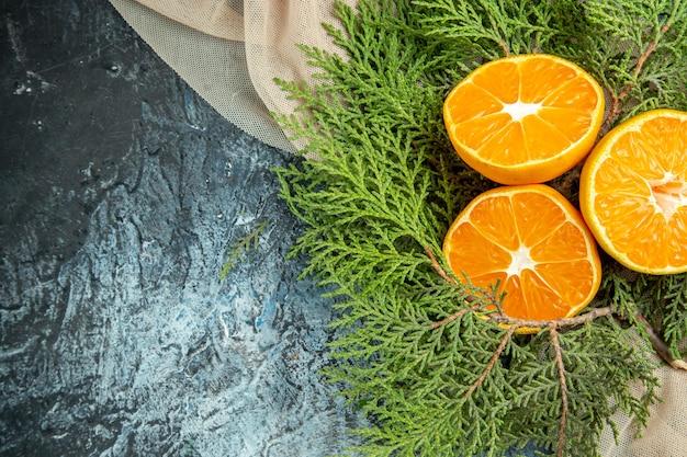 Bovenaanzicht gesneden sinaasappelen op beige sjaal op donkere ondergrond