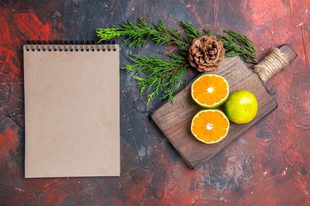 Bovenaanzicht gesneden sinaasappelen op de vertakking van de pijnboomboom met kegel een notitieboekje op donkerrood oppervlak