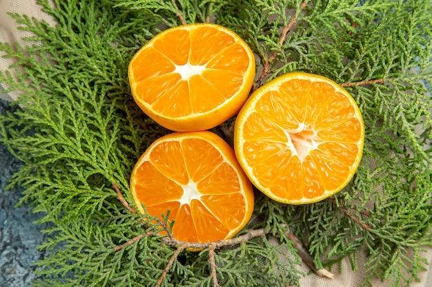 Bovenaanzicht gesneden sinaasappelen op dennentakken op donkere ondergrond