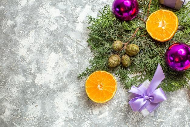 Bovenaanzicht gesneden sinaasappelen pijnboom takken kerstboom speelgoed kleine geschenken op grijze achtergrond