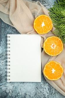 Bovenaanzicht gesneden sinaasappelen pijnboomtakken op beige sjaal kladblok op donkere ondergrond