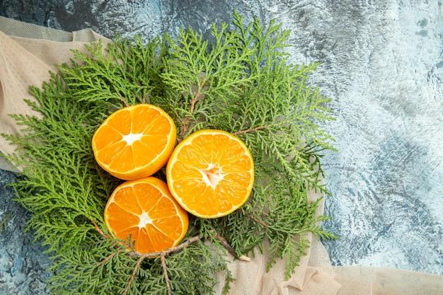 Bovenaanzicht gesneden sinaasappelen pijnboomtakken op beige sjaal op donkere ondergrond