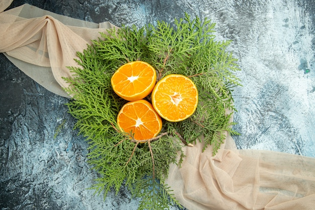 Bovenaanzicht gesneden sinaasappelen pijnboomtakken op beige sjaal op grijze oppervlakte vrije ruimte