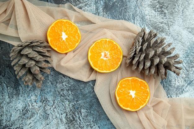 Bovenaanzicht gesneden sinaasappels dennenappels op beige sjaal op donkere ondergrond