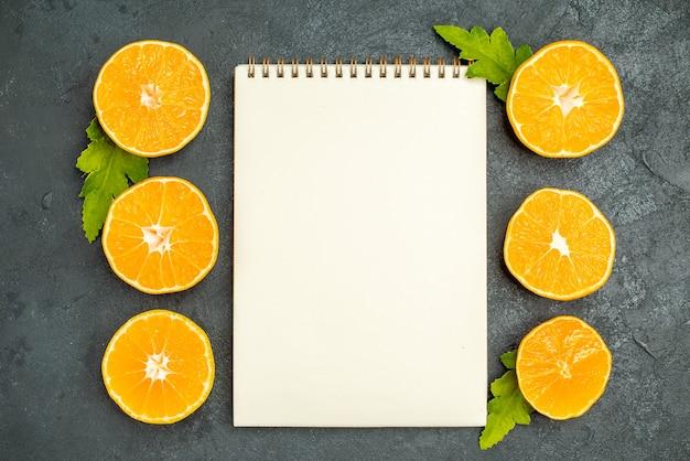 Bovenaanzicht gesneden sinaasappels een notitieboekje op donkere achtergrond