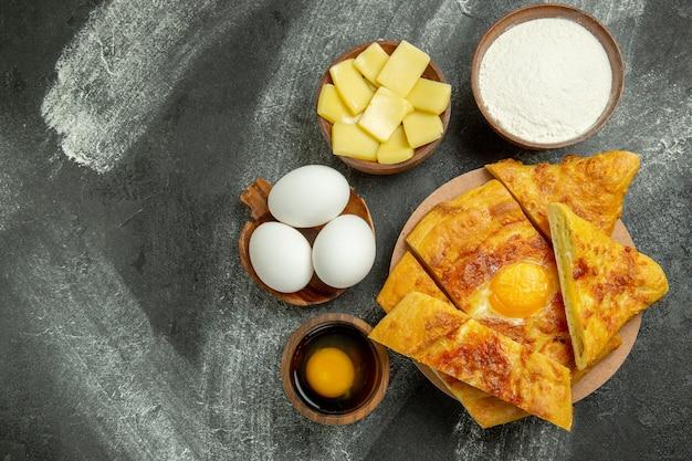 Bovenaanzicht gesneden taart met kaas op de grijze achtergrond voedsel maaltijd gebak bak oven zoet koekje