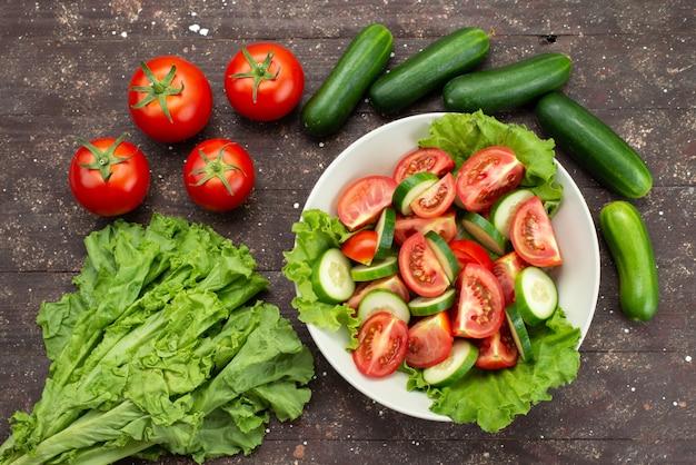 Bovenaanzicht gesneden tomaten met komkommers in witte plaat met groene salade op bruin, voedsel plantaardige verse salade