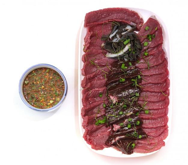 Bovenaanzicht gesneden vers rundvlees met thaise saus op wit.