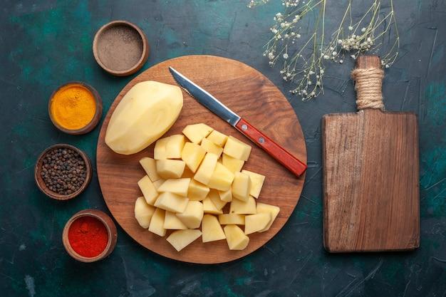 Bovenaanzicht gesneden verse aardappelen met kruiden op de donkerblauwe achtergrond