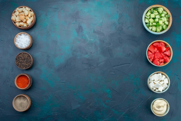 Bovenaanzicht gesneden verse groenten, komkommers en tomaten, samen met kruiden op de donkere achtergrond