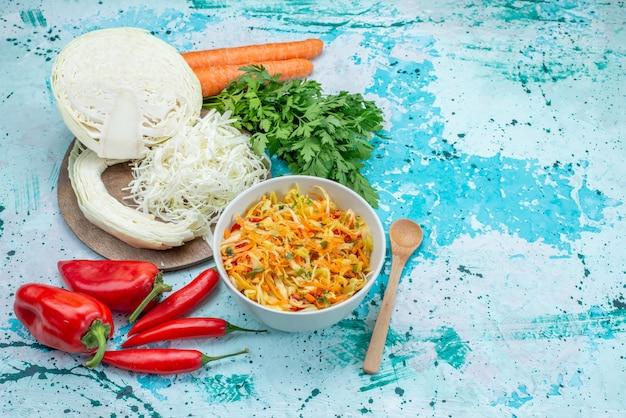 Bovenaanzicht gesneden verse groenten lange en dunne stukjes salade binnen plaat met groene kool paprika's op de helderblauwe achtergrond voedsel maaltijd groente salade snack
