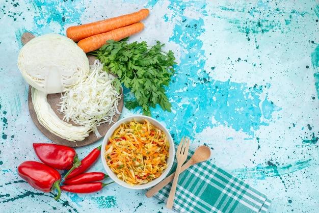Bovenaanzicht gesneden verse groenten lange en dunne stukjes salade binnen plaat met groene kool paprika's op de helderblauwe achtergrond voedsel maaltijd groente salade