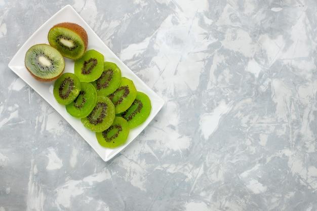 Bovenaanzicht gesneden verse kiwi's binnen plaat op de lichte witte achtergrond