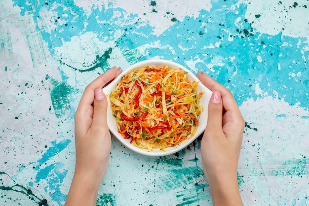 Bovenaanzicht gesneden verse salade groentesalade binnen plaatgreep door vrouwtje op het helderblauwe oppervlak maaltijd groente salade snack
