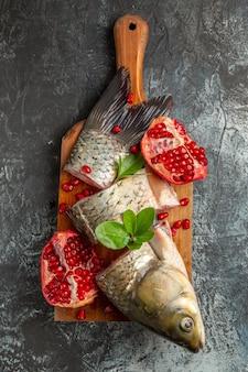 Bovenaanzicht gesneden verse vis met granaatappels op donkere ondergrond