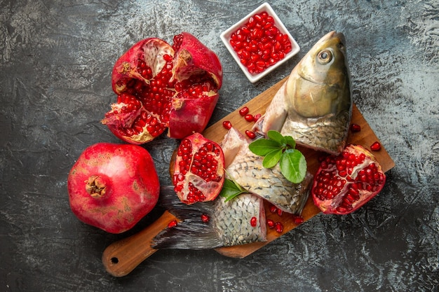 Bovenaanzicht gesneden verse vis met granaatappels op licht-donker oppervlak