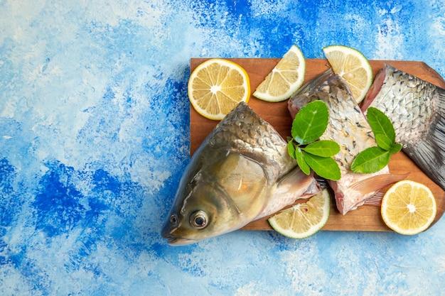 Bovenaanzicht gesneden verse vis met schijfjes citroen op het blauwe oppervlak