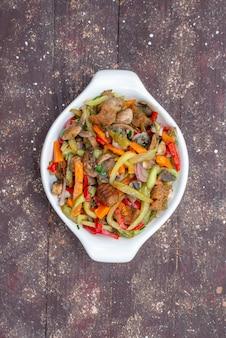 Bovenaanzicht gesneden vleesgerecht met gekookte groenten in plaat op de bruine houten tafel plantaardig voedsel maaltijd