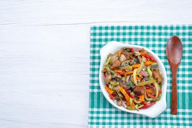 Bovenaanzicht gesneden vleesgerecht met gekookte groenten in plaat op de lichte tafel voedsel maaltijd plantaardig vlees