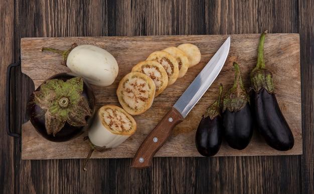Bovenaanzicht gesneden witte aubergine en zwart met mes op snijplank op houten achtergrond