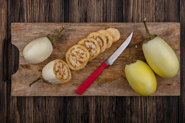 Bovenaanzicht gesneden witte aubergine met mes op snijplank op houten achtergrond
