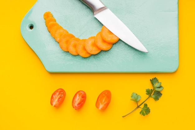 Bovenaanzicht gesneden wortel op snijplank met tomaten