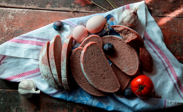 Bovenaanzicht gesneden zwart brood, eieren, pruimen, knoflook handschoenen en tomaten op een wit tafellaken.