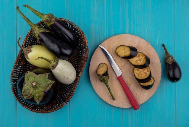 Bovenaanzicht gesneden zwarte aubergine op een snijplank met een mes en in een mand op een turkooizen achtergrond