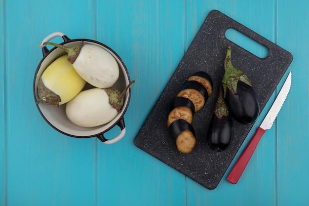Bovenaanzicht gesneden zwarte aubergine op een snijplank met een mes en witte aubergine in een pan op een turkooizen achtergrond
