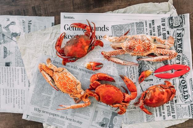 Bovenaanzicht gestoomde bloemkrabben en gigantische modderkrabben met gescheiden delen van gestoomde krab zoals klauwvlees en lijf op krantenpagina's.