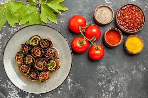 Bovenaanzicht gevulde aubergine rollen in witte plaat hete peper poeder kurkuma adjika tomaten op grijze achtergrond vrije ruimte