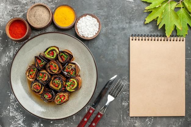 Bovenaanzicht gevulde aubergine rolt hete peperpoeder kurkuma in kleine kommen laat vork en mes een notitieboekje op grijs oppervlak