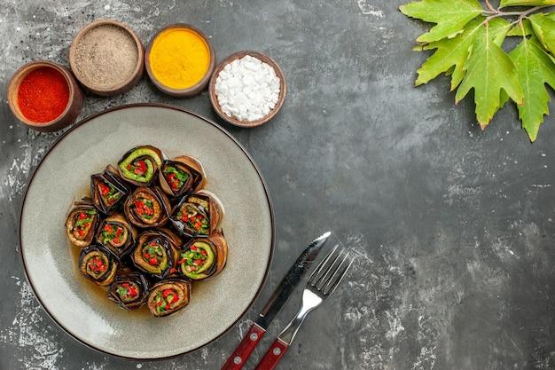 Bovenaanzicht gevulde aubergine rolt hete peperpoeder kurkuma in kleine kommen laat vork en mes op grijs oppervlak