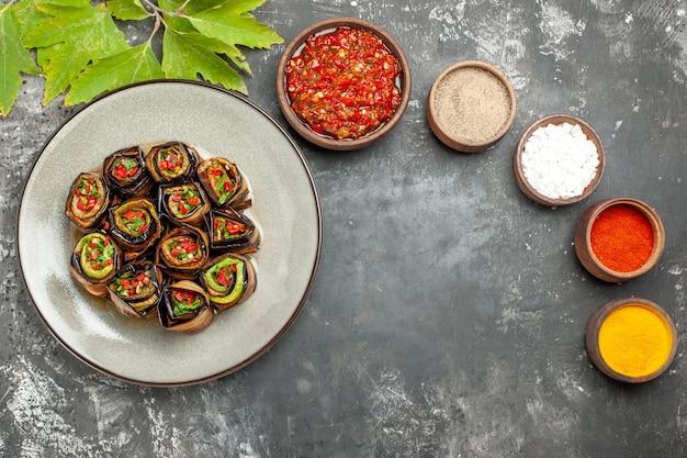 Bovenaanzicht gevulde aubergine rolt kruiden in kleine kommen zout peper rode peper kurkuma op grijze achtergrond