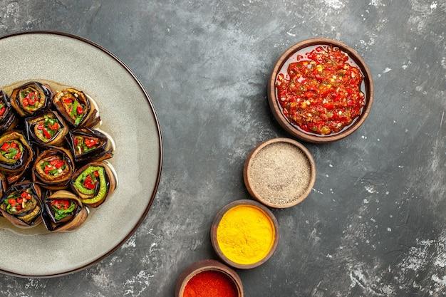 Bovenaanzicht gevulde auberginebroodjes in een bord met verschillende kruiden adjika in kleine kommen op grijs oppervlak