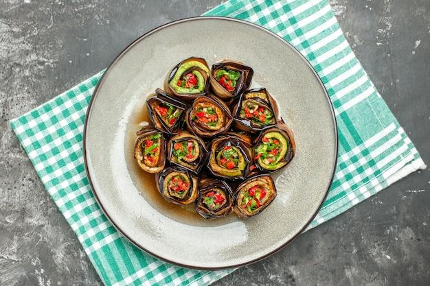 Bovenaanzicht gevulde auberginebroodjes in wit bord turquoise-wit tafelkleed op grijze achtergrond