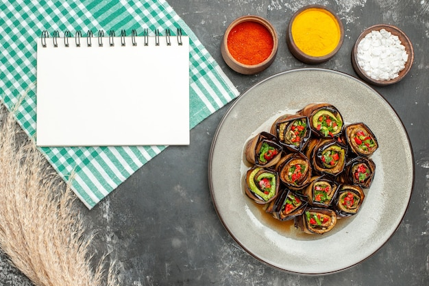 Bovenaanzicht gevulde auberginebroodjes in wit ovaal bord turkoois-wit tafelkleed verschillende kruiden een notitieblok op grijs oppervlak