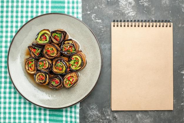 Bovenaanzicht gevulde auberginebroodjes in wit ovaal bord turquoise-wit tafelkleed een notitieboekje op grijs oppervlak
