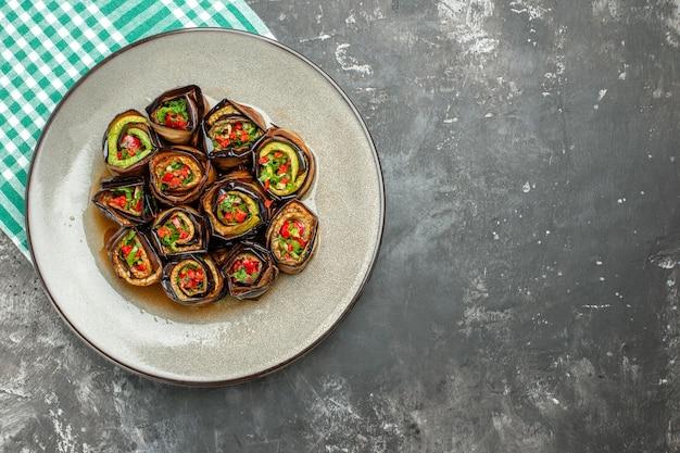Bovenaanzicht gevulde auberginebroodjes in wit ovaal bord turquoise-wit tafelkleed op grijs oppervlak