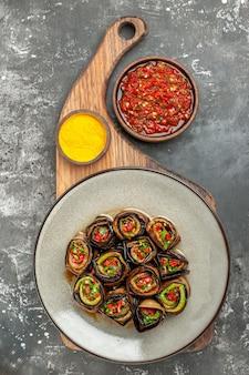 Bovenaanzicht gevulde auberginebroodjes in witte ovale plaat kurkuma in kom op houten dienblad met handvat adjika op grijze achtergrond