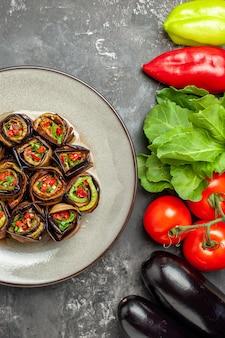 Bovenaanzicht gevulde auberginebroodjes in witte plaat tomaten, paprika's, aubergines op grijze achtergrond