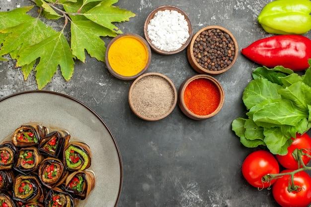 Bovenaanzicht gevulde auberginebroodjes in witte plaat tomaten, paprika's, aubergines, verschillende kruiden op grijze achtergrond